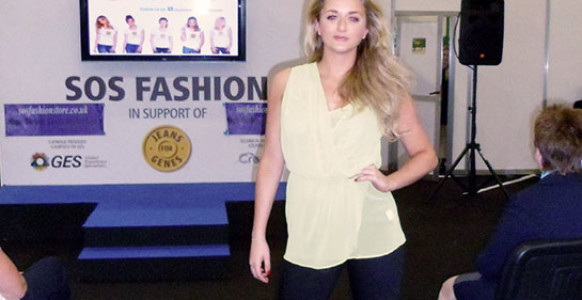 model at a fashion show with 'sos fashion' company name in background